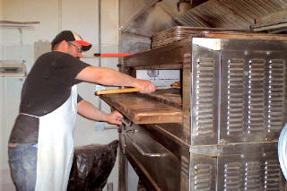 Brian Spangler taking one of his pizzas out of the oven at Apizza Scholls.