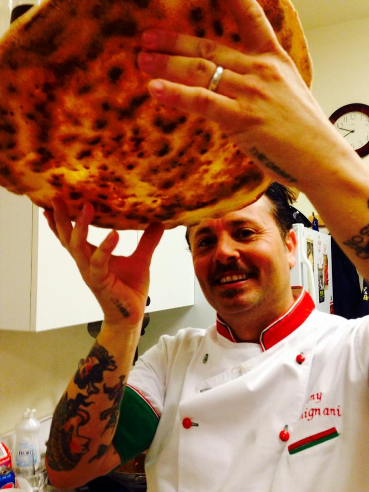 Tony inspects the bottom of a pizza in New york
