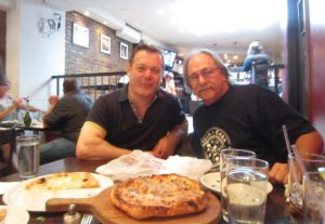 Roberto Caporuscio and Albert Grande share a pizza.